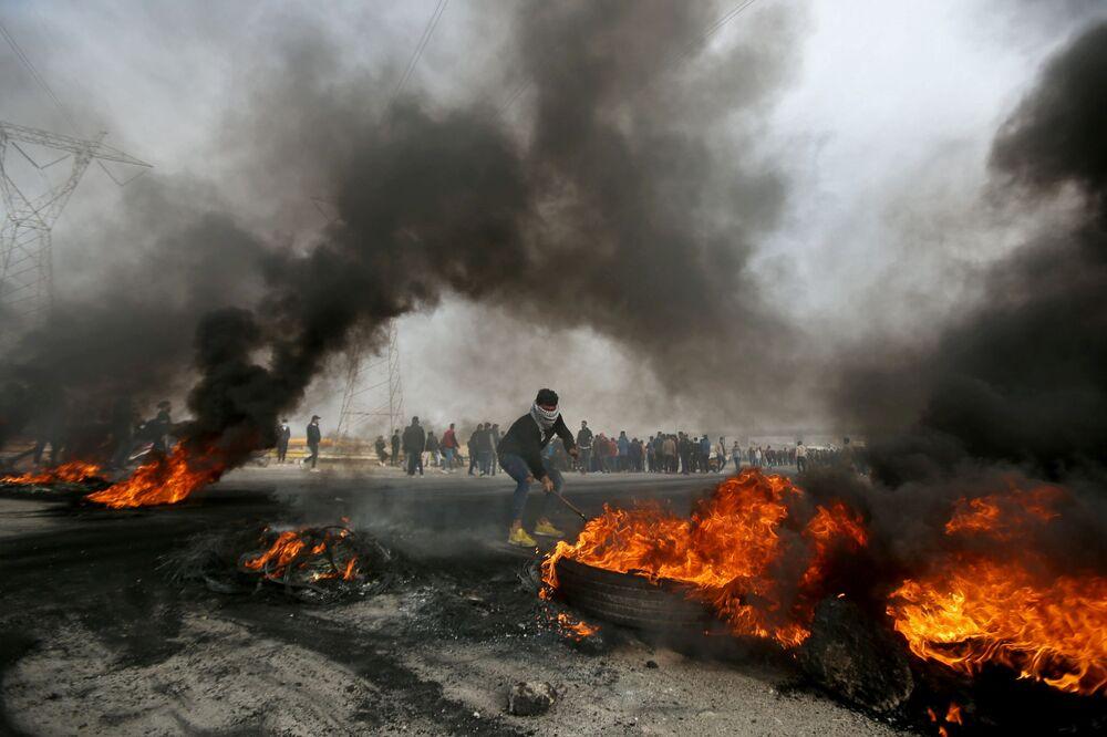 متظاهر عراقي يحرك إطارات محترقة خلال احتجاجات مناهضة للحكومة في البصرة  العراق، 20 ديسمبر 2020