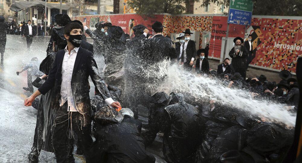 أطلقت الشرطة الإسرائيلية خراطيم المياه باتجاه اليهود المتدينين، الذين أغلقوا الطريق خلال مظاهرة في القدس، 22 ديسمبر 2020.