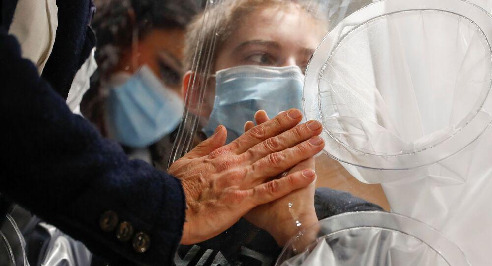 طفل في المستشفى يلامس يد والده من خلال حاجز بلاستيكي لمنع تعرضه لخطر التلوث أو انتقال مرض (كوفيد-19) في قسم إعادة تأهيل الأطفال وإعاقات النمو في مستشفى سان رافاييل، وذلك في إطار تلبية  رغبة الأطفال في رؤية أقاربهم وعناقهم في عيد الميلاد المجيد في روما، إيطاليا، 22 ديسمبر 2020.