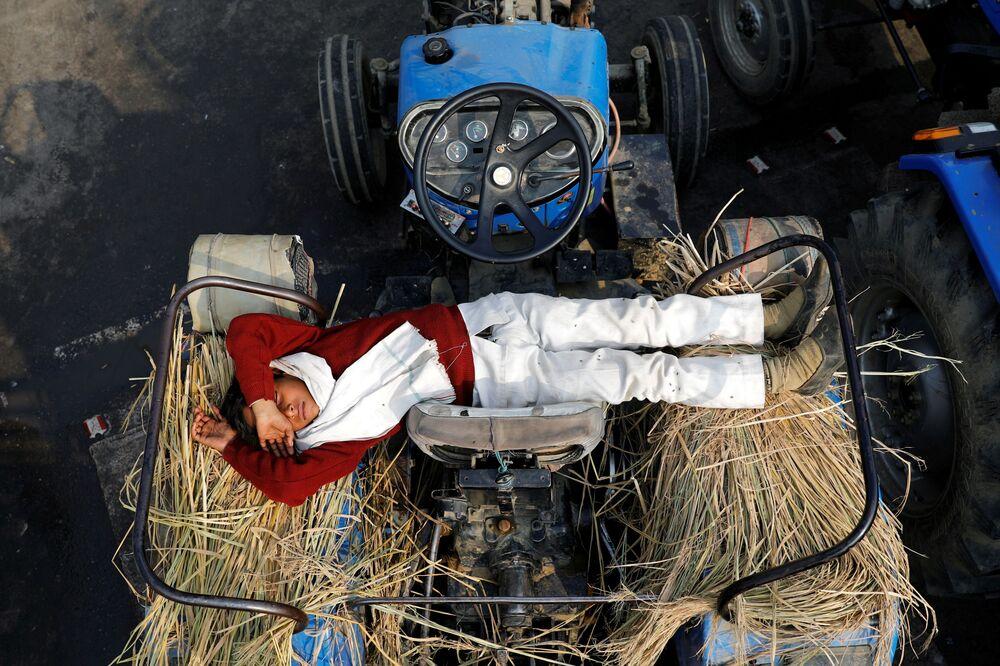 نجل مزارع ينام على جرار في موقع احتجاجات ضد قوانين الزراعة الجديدة، عند حدود دلهي وأوتار براديش في غازي آباد، الهند، 23 ديسمبر 2020