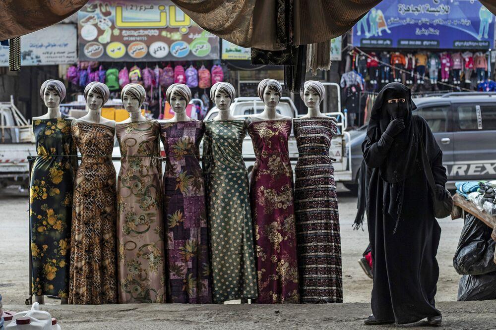 امرأة تمر أمام أزياء معروضة في مدينة الرقة شمال سوريا، 20 ديسمبر 2020