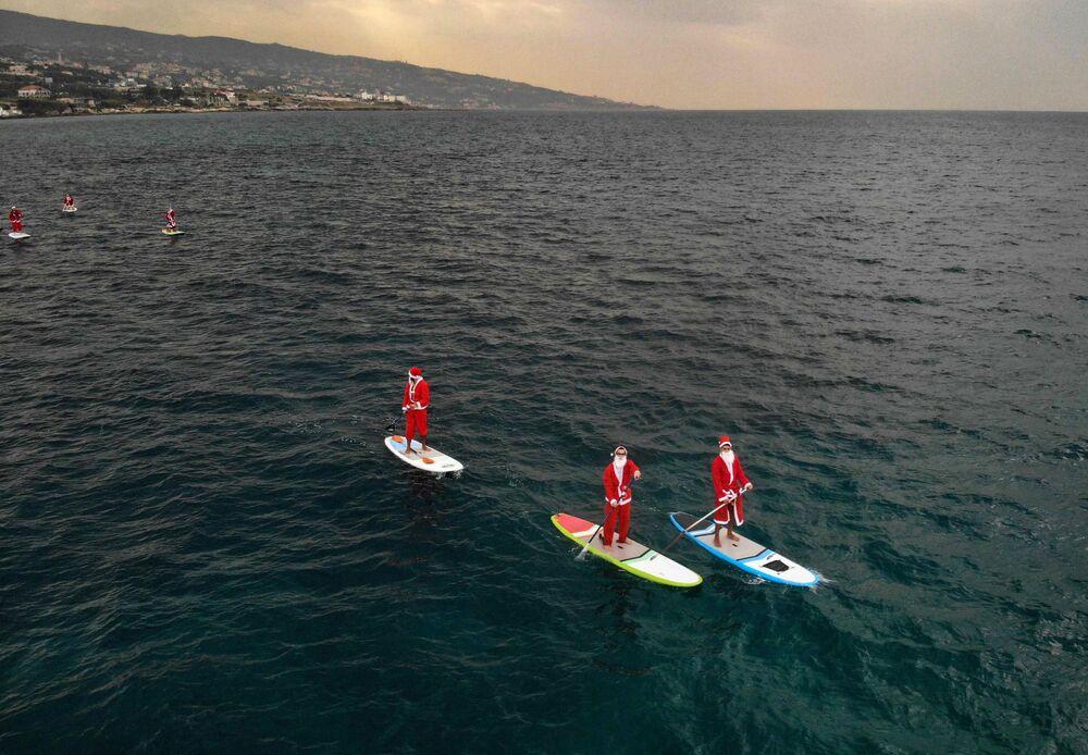 لبنانيون يرتدون ملابس بابا نويل يركبون مجدافاً في مدينة البترون الساحلية شمال لبنان، 22 ديسمبر 2020