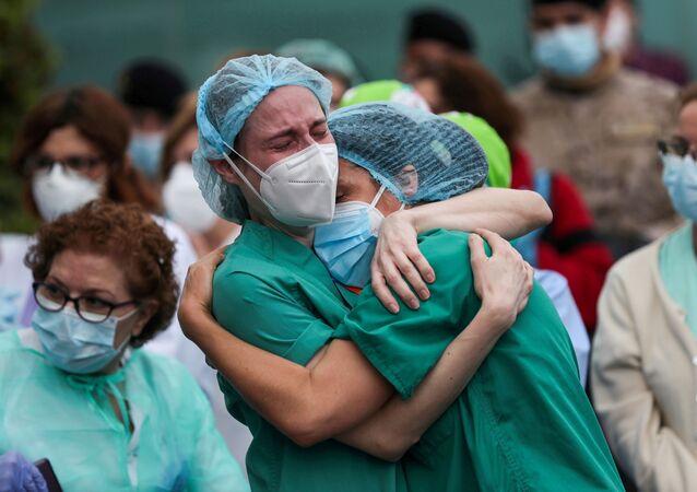 عاملون طبيون يبكون خلال تكريم زميلهم المتوفى خلال جائحة كورونا في ليغانيس بإسبانيا