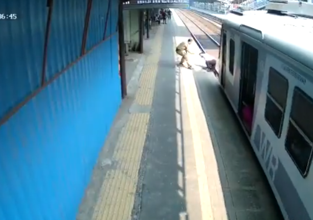 شرطي في مومباي يساعد رجلا علق على السكك الحديدية