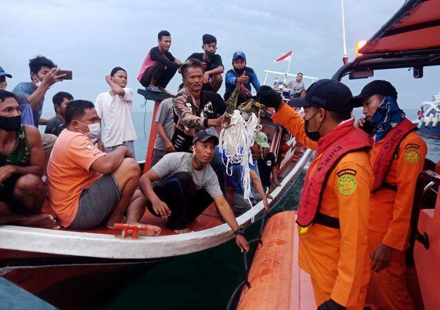 الصيادون المحليون وعمال الإنقاذ يحتفظون بقايا مشتبه بها لرحلة طائرة سريويجايا الجوية SJ182 ، التي تحطمت في البحر بالقرب من جاكرتا