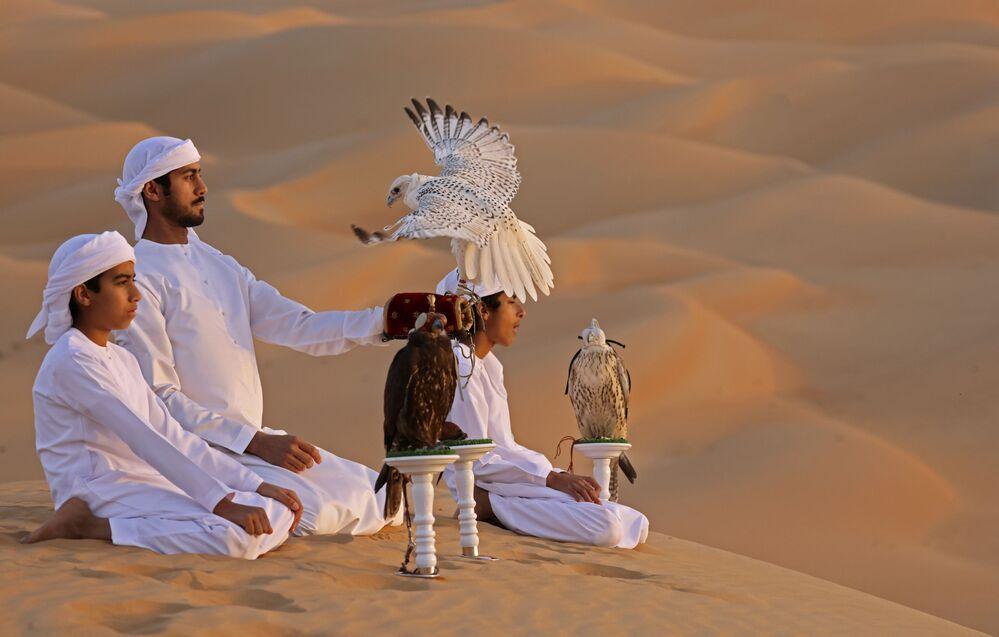 الإماراتي علي منصوري (الثاني من اليسار) يدرب صقاراً في صحراء ليوا، على بعد حوالي 250 كيلومترا غرب إمارة أبو ظبي الخليجية، 9 يناير 2021