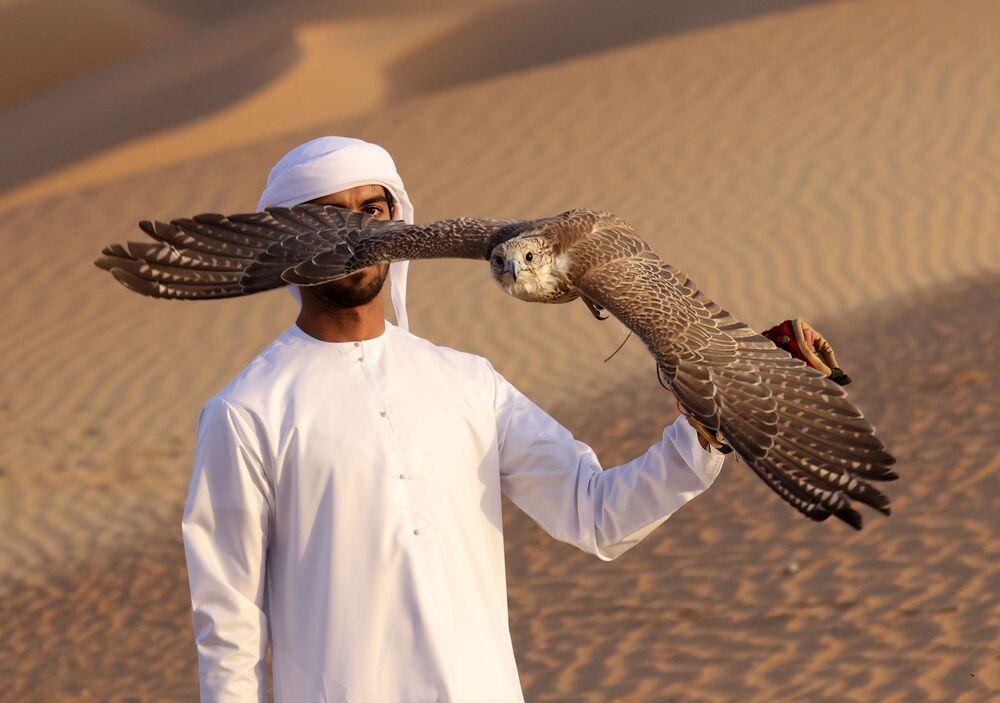 الإماراتي علي منصوري خلال تدريب الصقور في صحراء ليوا، على بعد حوالي 250 كيلومترا غرب إمارة أبو ظبي الخليجية، 9 يناير 2021