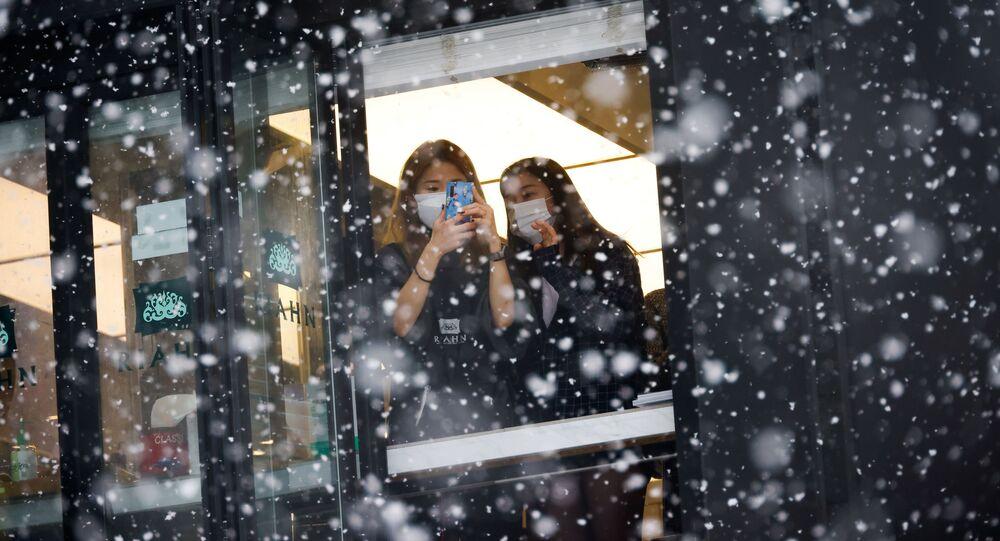 امرأة تلتقط صوراً لتساقط الثلج من نافذتها خلال تساقط الثلوج الكثيفة، وسط جائحة فيروس كورونا (كوفيد-19) في سيئول، كوريا الجنوبية، 12 يناير 2021