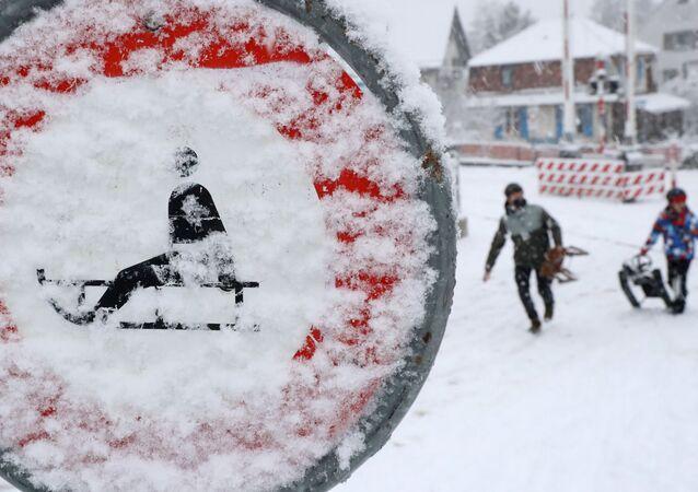 أشخاص يحملون زلاجات يسيرون أمام لافتة مرور مغطاة بالثلوج، مع استمرار انتشار فيروس كورونا (كوفيد-19) في زيورخ، سويسرا، 12 يناير 2021