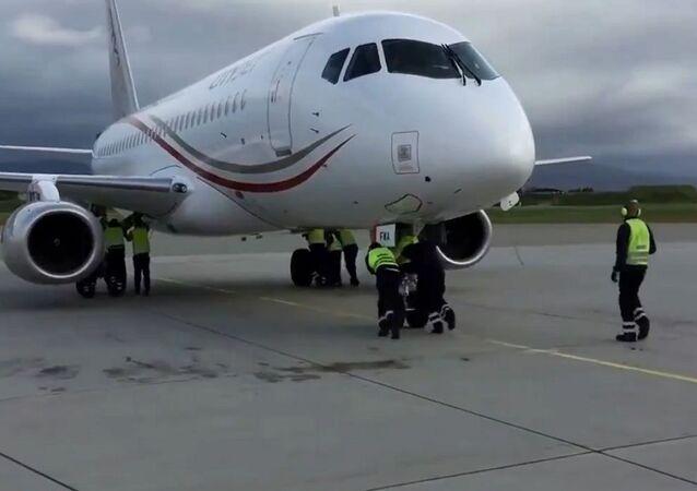 مجموعة من الأشخاص يحركون طائرة متوقفة