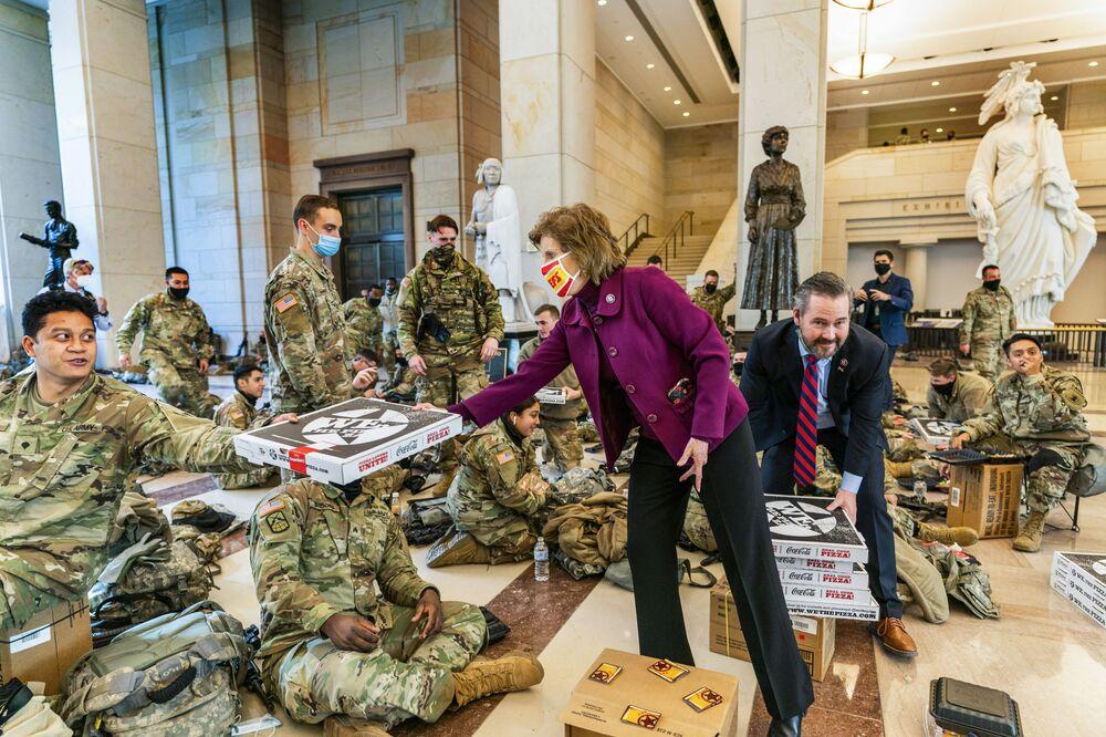 عضوا مجلس النواب الأمريكي فيكي هارتزلر ومايكل والتز يقومان بتوزيع البيتزا على عناصر قوات الحرس الوطني الأمريكي في مبنى الكابيتول، واشنطن 13 يناير 2021
