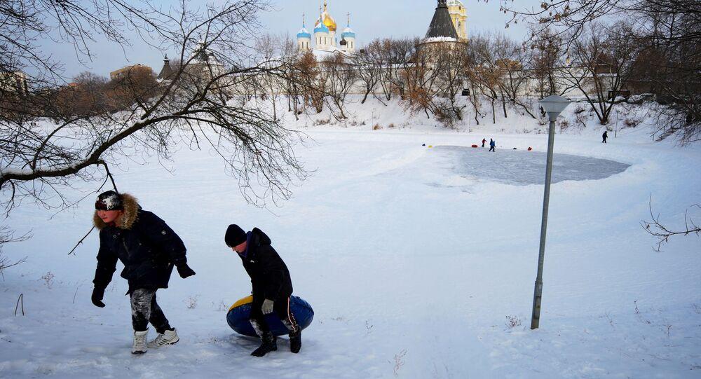 أطفال يمرحون على بحيرة متجمدة بالقرب من دير نوفوسباسكي في موسكو، 13 يناير 2021