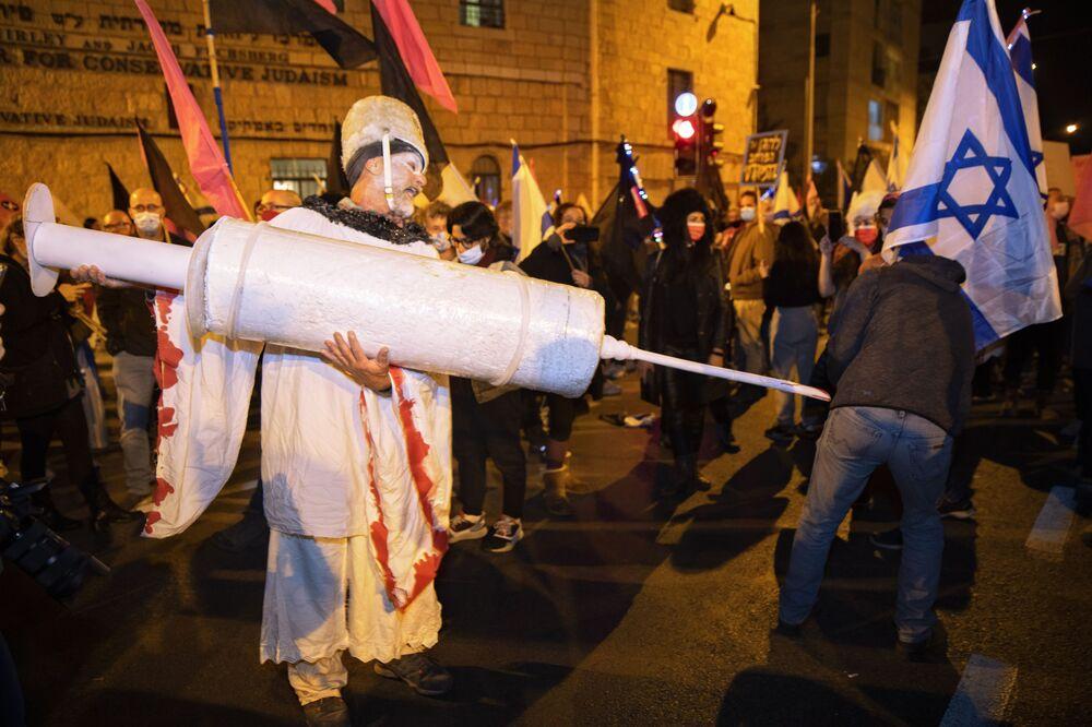 متظاهر إسرائيلي يحمل حقنة عملاقة خلال احتجاجات ضد رئيس الوزراء الإسرائيلي بنيامين نتنياهو بالقرب من مقر إقامته الرسمي في القدس، وسط الإغلاق الثالث لفيروس كورونا على مستوى البلاد، 9 يناير 2021.