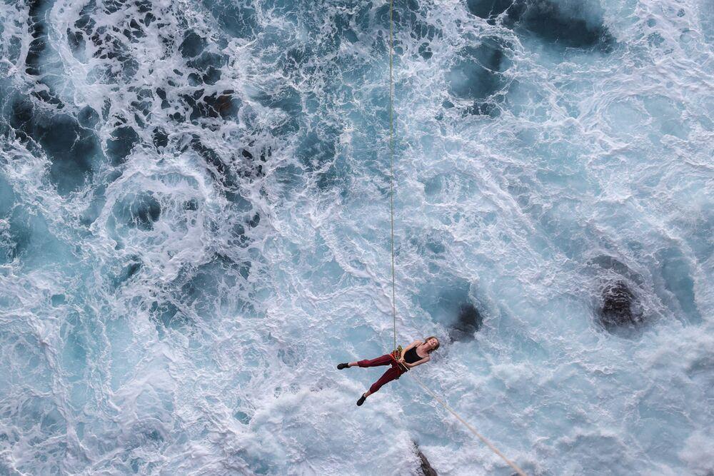إحدى عشاق رياضة المغامرات تتأرجح على حبل فوق المحيط بعد القفز من حافة جرف أثناء القفز بالحبل بالقرب من كورارونغ، أستراليا، 9 يناير 2021.