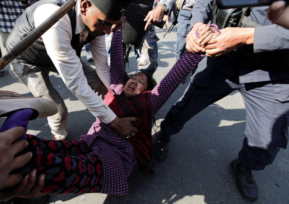 أحد أنصار النظام الملكي، خلال الاحتفال بالذكرى السنوية لميلاد الملك الراحل بريثفي نارايان شاه الذي شكل نيبال الحالية منذ قرون، يتم مساعدته بعد إصابته خلال اشتباكات مع شرطة مكافحة الشغب وسط خلاف حول مسار التجمع في كاتماندو، نيبال 11 يناير 2021 .