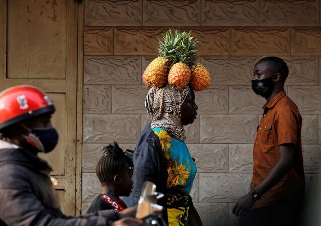امرأة تسير وهي تحمل فاكهة الأناناس على رأسها في أحد شوارع كمبالا، أوغندا 12 يناير 2021