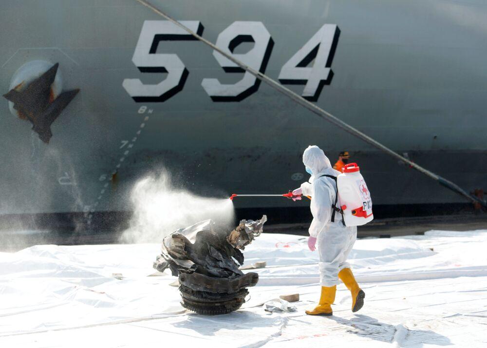 عضو في الصليب الأحمر الإندونيسي يقوم بتعقيم قطعة من الحطام تم استردادها من البحر، يعتقد أنها من توربين رحلة طيران سريويجايا SJ182 التي تحطمت في البحر، في جاكرتا، إندونيسيا، 11 يناير 2021