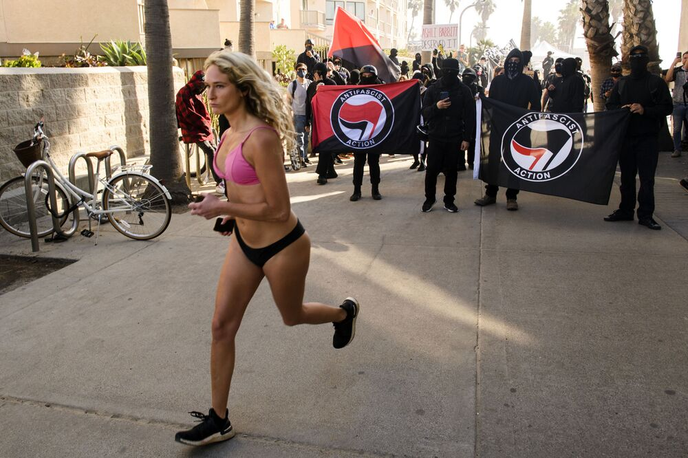 امرأة تركض أمام متظاهرين مناهضين، بعضهم يحمل أعلام حركو أنتيفا، في انتظار مواجهة مظاهرة باتريوت مارش لدعم الرئيس الأمريكي دونالد ترامب، بالقرب من رصيف الكريستال في 9 يناير 2021 في حي باسيفيك بيتش في سان دييغو، كاليفورنيا .