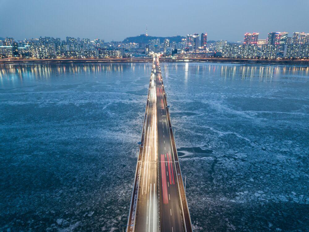 تُظهر صورة تم التقاطها في 10 يناير 2021 منظرًا عامًا لحركة المرور التي تمر فوق جسر فوق نهر هان المتجمد على خلفية مدينة سيئول، كوريا الجنوبية 10 يناير 2021