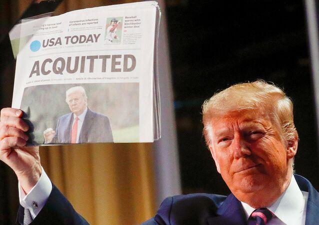 Альт: الرئيس الأمريكي، دونالد ترامب، يحمل  نسخة من الصفحة الأولى لصحيفة يو إس إيه توداي تظهر أنباء تبرئته في محاكمة عزله في مجلس الشيوخ 6 فبراير 2020