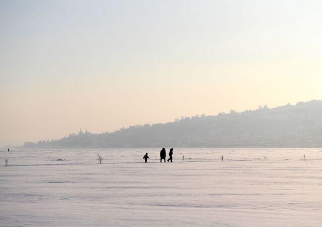 امرأة وأطفال يسيرون على جليد نهر الفولغا، روسيا 13 يناير 2021