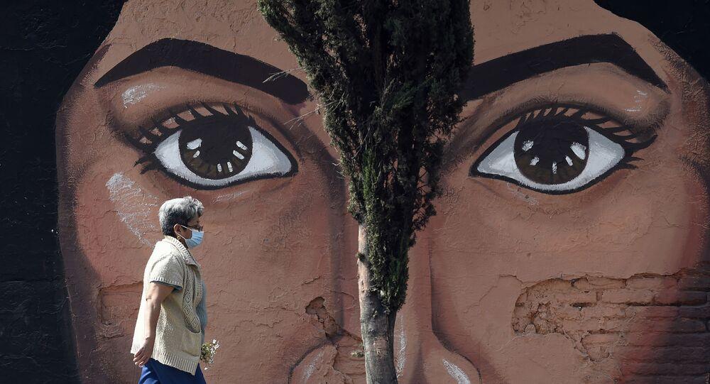امرأة ترتدي قناعًا للوجه تمشي بجوار لوحة جدارية على أحد جدران مقبرة سان نيكولاس تولينتينو في بلدية إيزتابالابا في مكسيكو سيتي في 15 يناير 2021، وسط جائحة فيروس كورونا الجديد كوفيد-19.