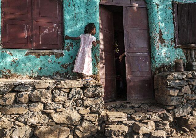 فتاة تنظر داخل منزل بينما يخرج شخص ما يده لها في مدينة جوندر، إثيوبيا، 17 يناير 2021