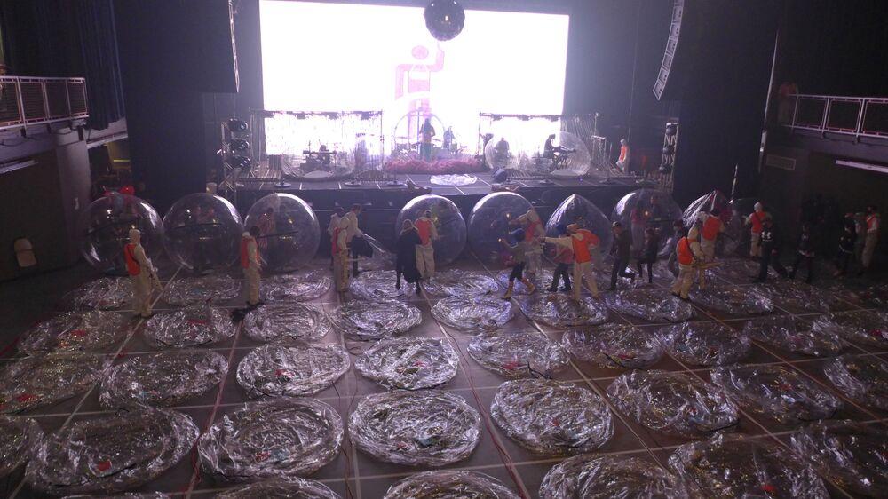 موظفون يقومون يبتكبير الفقاعات البلاستيكية، المستخدمة كإجراء احترازي لمنع انتشار فيروس كورونا (المسبب لمرض كوفيد-19)، خلال حفل موسيقي لفرقة فلايمينغ ليبس (Flaming Lips) وفق قاعدة التباعد الاجتماعي في كريتيريون في أوكلاهوما سيتي، الولايات المتحدة، 22 يناير 2021