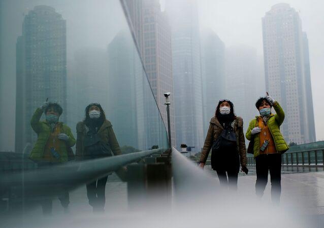 أشخاص يرتدون كمامات يسيرون في أحد الشوارع وسط تفشي مرض فيروس كورونا (كوفيد-19) في شنغهاي الصين، 26 يناير 2021