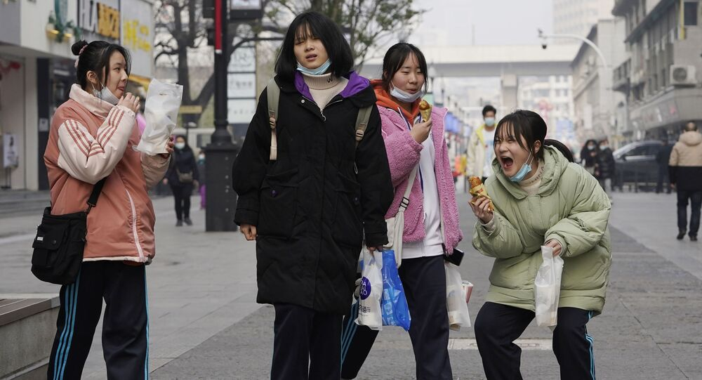 تستمتع الفتيات الصغيرات بلحظات صغيرة أثناء زيارتهن لحي التسوق الشهير في مدينة ووهان بمقاطعة هوبي بوسط الصين، 26 يناير 2021.