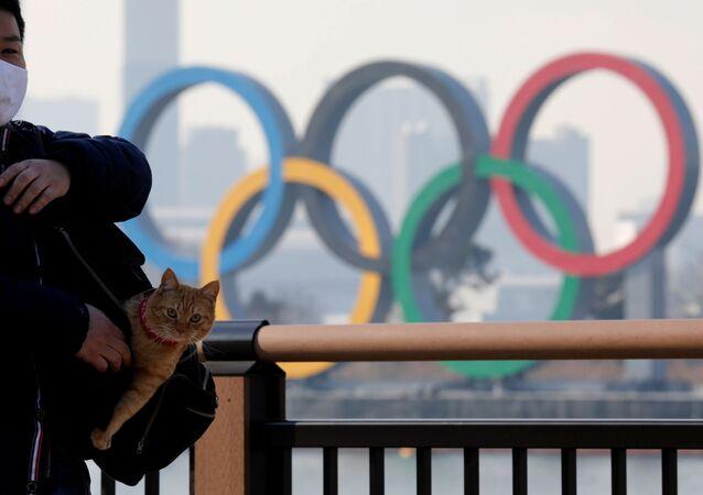 رجل يحمل قطة في حقيبته يقف على خلفية الحلقات الأولمبية العملاقة وسط تفشي مرض فيروس كورونا (كوفيد-19) في طوكيو، اليابان، 22 يناير 2021