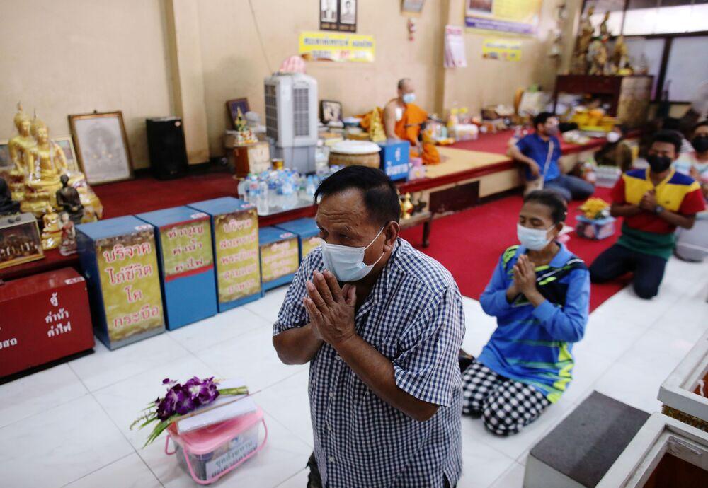 المصلون قبل الدخول إلى التوبيت للصلاة والدعاء لـ خداع الموت وتحسين حظهم في معبد في بانكوك، تايلاند، 27 يناير 2021