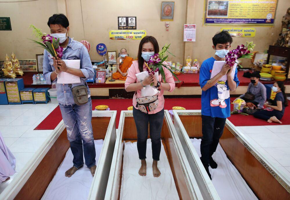 المصلون يستلقون ويصلون داخل توابيت لـ خداع الموت وتحسين حظهم في معبد في بانكوك، تايلاند، 27 يناير 2021