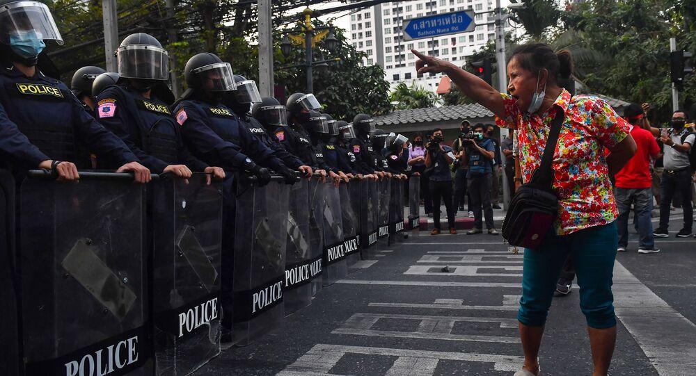 متظاهرة مؤيدة للديمقراطية تشير بأصبعها إلى شرطة مكافحة الشغب بالإنصراف،  بانكوك في 1 فبراير 2021، بالقرب من مكان تظاهر فيه مهاجرون من ميانمار بعد الانقلاب العسكري في ميانمار.