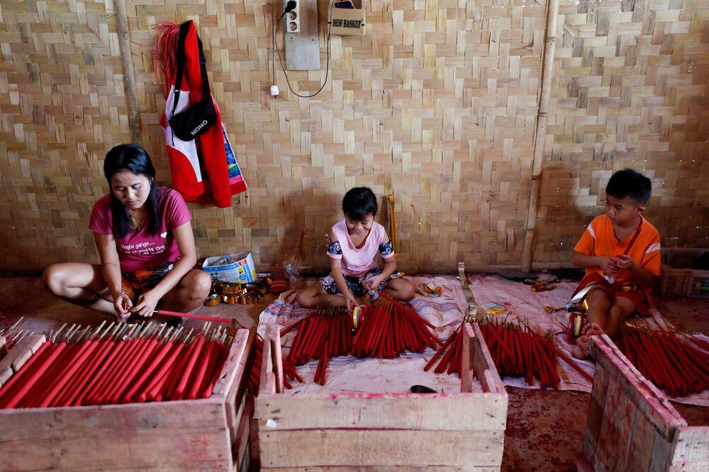 الإخوة كايلا راني (9 أعاوم)  وجوسا ناتانايل (7 أعوام) ، يحضران أعواد البخور، قبل السنة القمرية الصينية الجديدة، في تانجيرانج، في ضواحي جاكرتا، إندونيسيا، 10 فبراير 2021