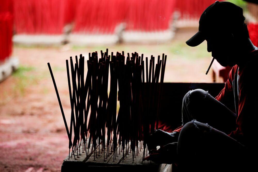 عامل في مصنع بأعواد البخور، قبل السنة القمرية الصينية الجديدة، في تانجيرانج، في ضواحي جاكرتا، إندونيسيا، 10 فبراير 2021