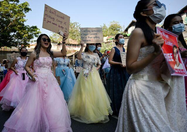 نساء ميانمار يرتدين فساتين الزفاف يحملن لافتات خلال احتجاج ضد الانقلاب العسكري الذي حدث في 1 فبراير/ شباط في العاصمة يانغون، 10 فبراير 2021