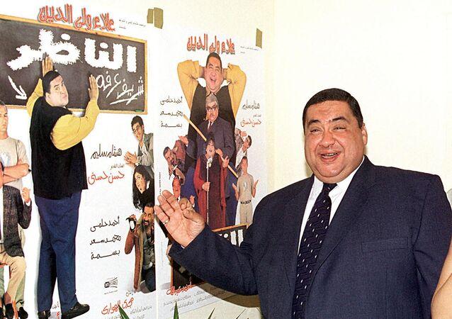 الفنان المصري، علاء ولي الدين، يقف أمام الملصق الدعائي لفيلمه الشهير الناظر في العاصمة المصرية القاهرة، 2000