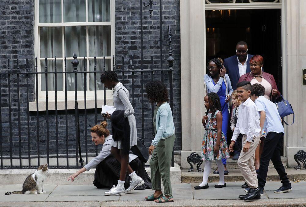 تلاميذ المدارس يحاولون ملاعبة القط لاري بعد الانتهاء من لقاء رئيس الوزراء البريطاني بوريس جونسون في 10 داونينج ستريت في لندن، المملكة المتحدة 30 أغسطس 2019