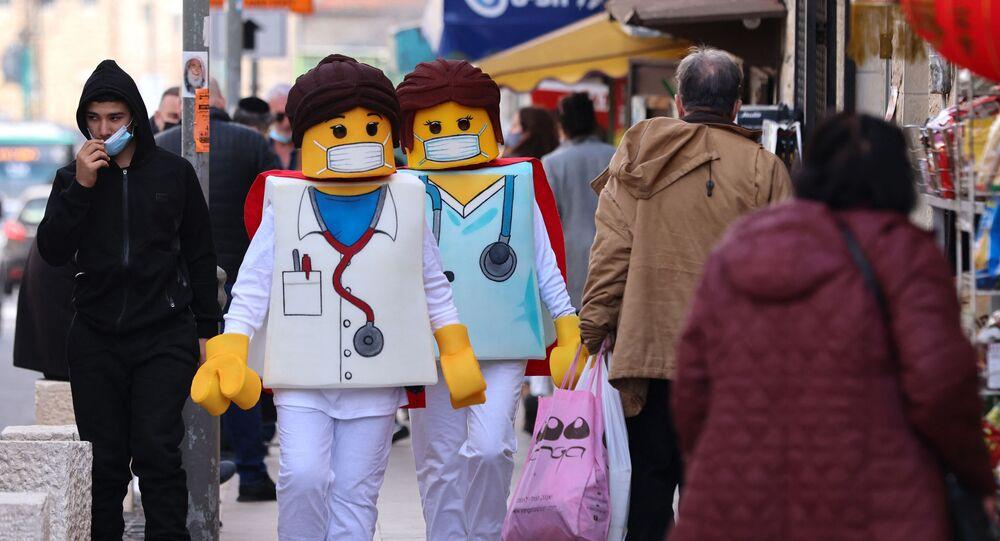 أشخاص يرتدون زي ليغو يسيرون أمام المحلات التجارية في القدس، 24 فبراير 2021