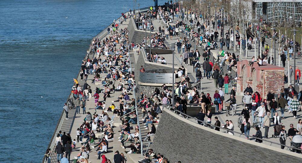 يقضي الناس وقتًا تحت أشعة الشمس على ضفاف نهر الراين وسط جائحة كورونا (كوفيد-19) في مدينة كولونيا في ألمانيا، 21 فبراير 2021.