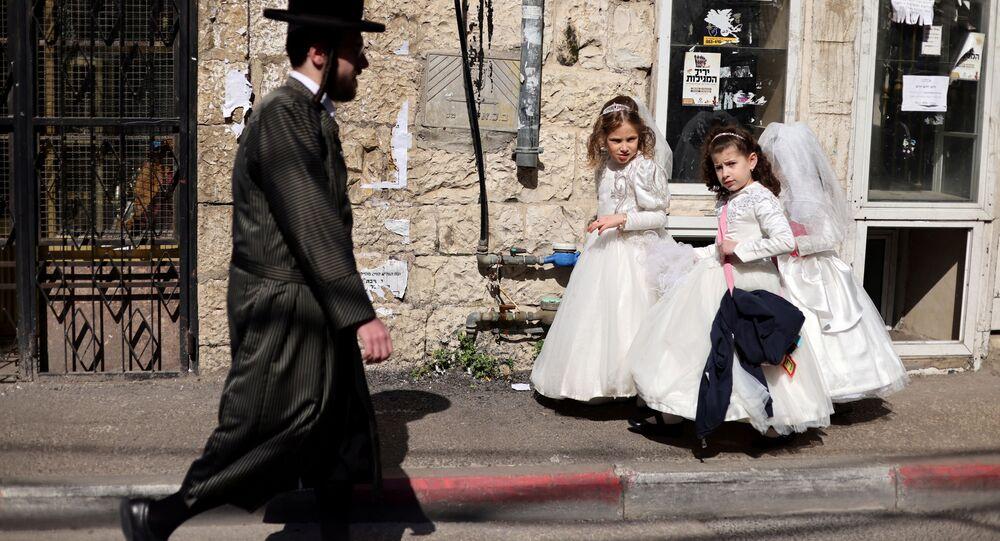 فتيات يرتدين أزياء تنكرية للاحتفال بعيد بوريم (المساخر) اليهودي ، وهو احتفال بخلاص اليهود من الإبادة الجماعية في بلاد فارس القديمة، يسيرون على رصيف في حي ميا شعاريم اليهودي الأرثوذكسي المتطرف في القدس، 24 فبراير 2021