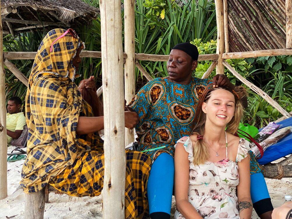 سكان محليون يصنعون االضفائر لفتاة على الشاطئ في جزيرة زنجبار، تنزانيا 18 فبراير 2021