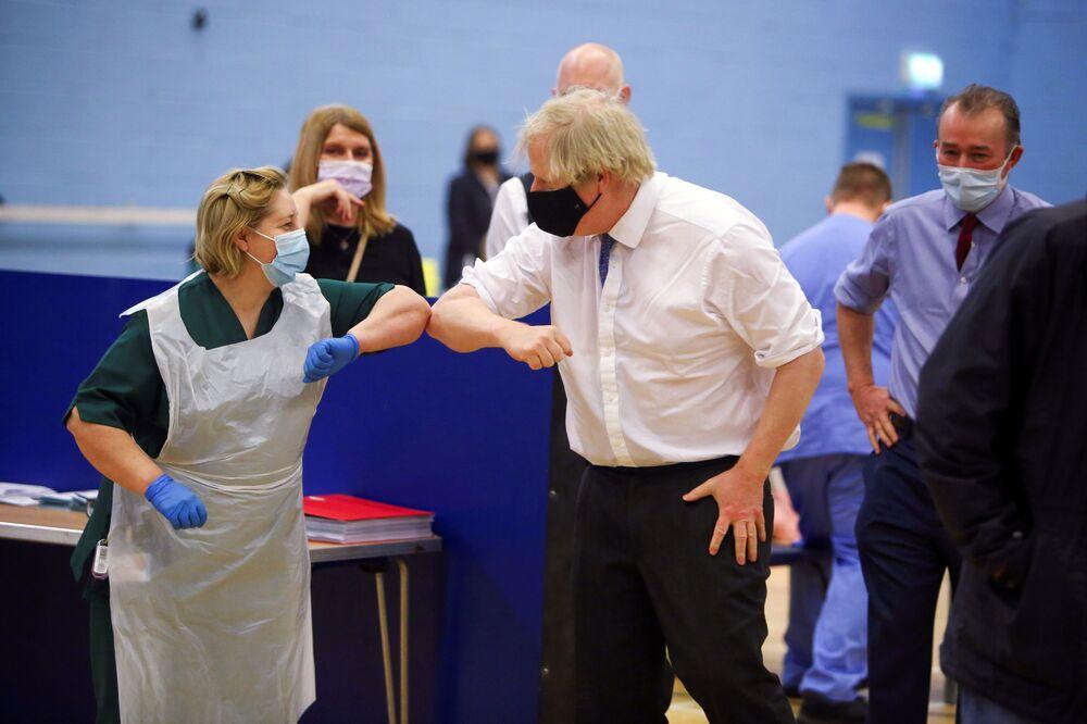 رئيس الوزراء البريطاني بوريس جونسون يحيي الممرضة لويز غراي خلال زيارته لمركز التطعيم ضد فيروس كورونا (كوفيد-19) في ملعب كومبران في كومبران، جنوب ويلز، بريطانيا في 17 فبراير 2021.