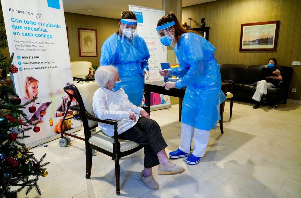 موظفة في دار المسنين إل فيسو تتحدث مع أماليا غونزاليس، 96 عاماً، قبل حقنها بجرعة من لقاح فايزر ضد كوفيد-19 في مدريد، إسبانيا، 7 يناير 2021.