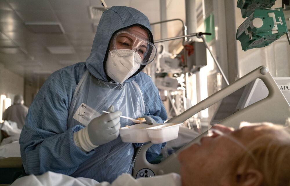ممرضة تقوم بإطعام مريض في وحدة العناية المركزة بالمستشفى السريري باسم أو. ام. فيلاتوف رقم 15 في موسكو، 8 ديسمبر 2020