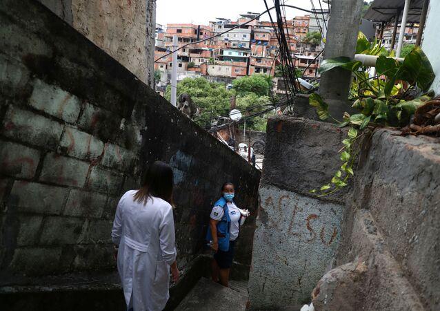 موظفو الرعاية الصحية يحملون مبردًا يحتوي على جرعات من لقاح ضد فيروس كورونا (كوفيد-19) من لقاح سينوفاك، أثناء زيارتهم لكبار السن الذين لا يستطيعون مغادرة منازلهم، في حي تورانو الفقير في ريو دي جانيرو، البرازيل، 8 فبراير 2021