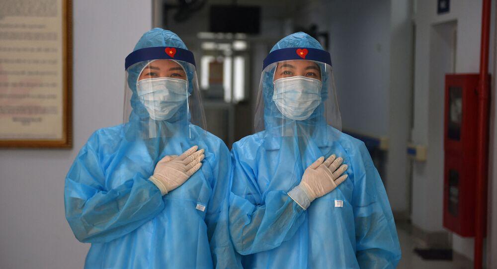 عمال الصحة يرتدون أزياء واقية يقفون لالتقاط صورة في مركز طبي مؤقت لاستقبال مرضى فيروس كورونا كوفيد-19 في هانوي، فيتنام 30 يوليو 2020