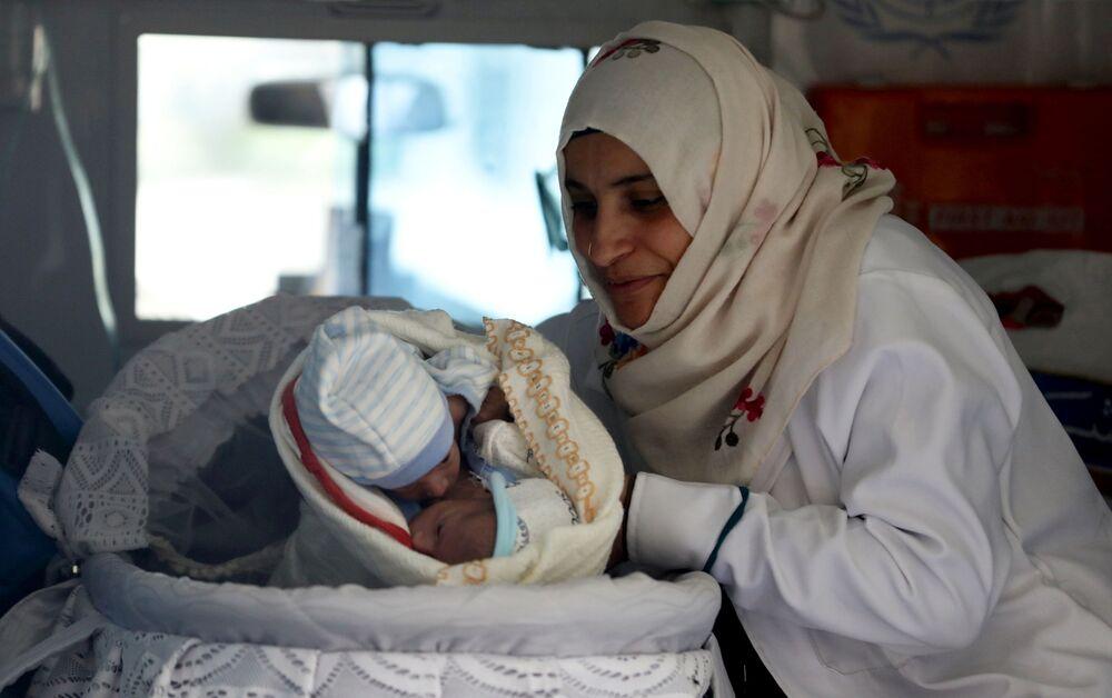 ممرضة تحمل توأمات ملتصقان، محمد وأحمد ياسر البخيتي، داخل سيارة إسعاف في مطار صنعاء، في انتظار نقلهما جواً لإجراء جراحة فصل في الأردن، صنعاء، اليمن، 6 فبراير 2021