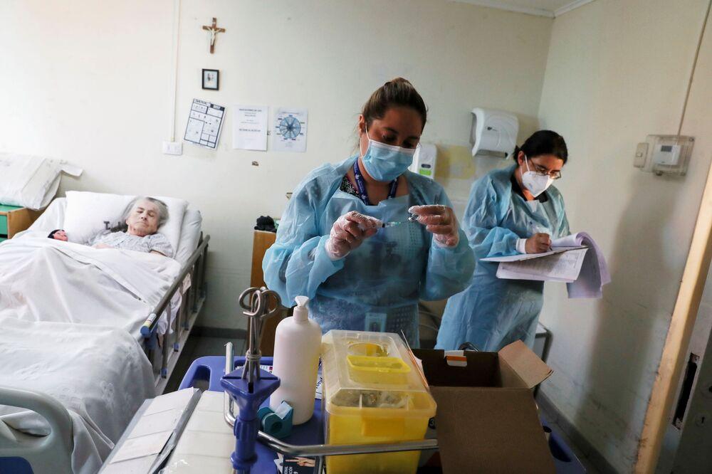 يستعد العاملون في الرعاية الصحية لإعطاء جرعة من لقاح سينوفاك ضد فيروس كورونا (كوفيد-19)، حيث تبدأ تشيلي في تطعيم كبار السن الذين يعيشون في دور رعاية المسنين في سانتياغو، تشيلي، 4 فبراير 2021